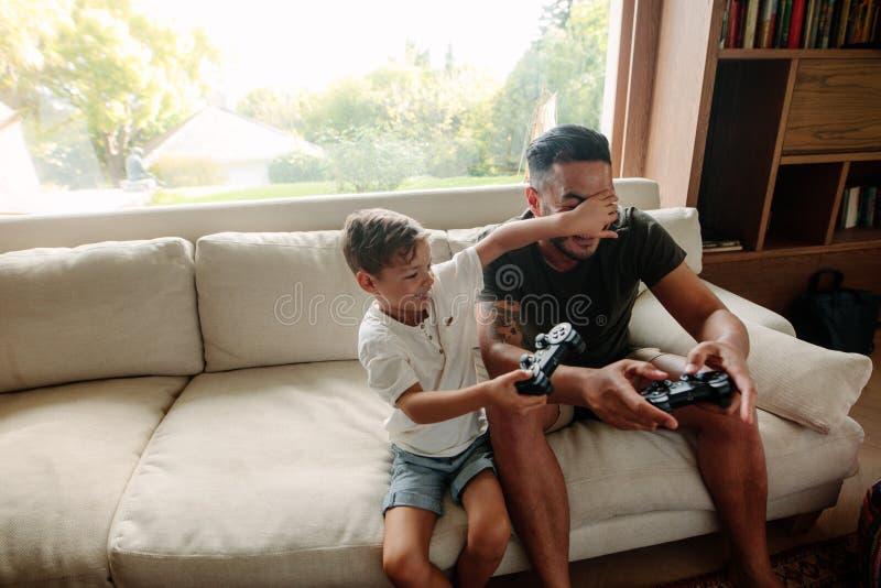 Pai e filho que têm o divertimento que joga jogos de vídeo em casa imagem de stock royalty free