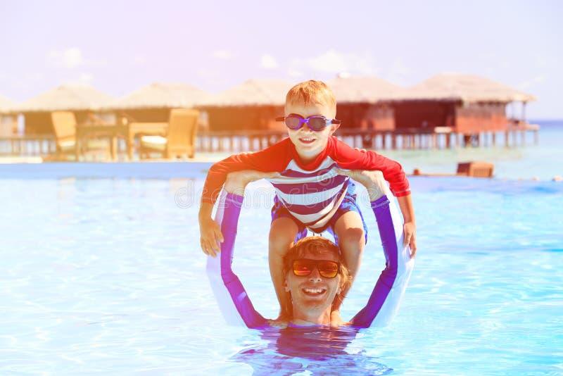 Pai e filho que têm o divertimento na piscina imagens de stock