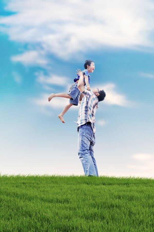 Pai e filho que têm uma estadia da qualidade ao ar livre foto de stock royalty free