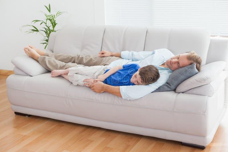 Pai e filho que usa a dormida no sofá fotografia de stock royalty free