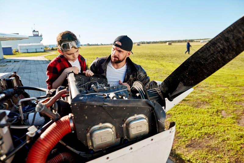 Pai e filho que verificam junto o armário do motor antes do voo imagem de stock