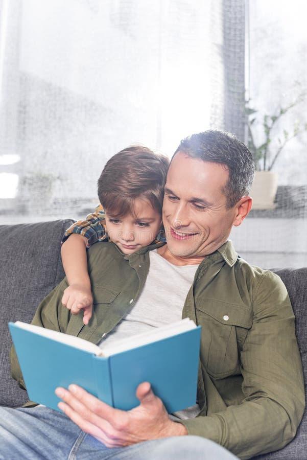 pai e livro de leitura adorável do filho junto ao sentar-se fotos de stock