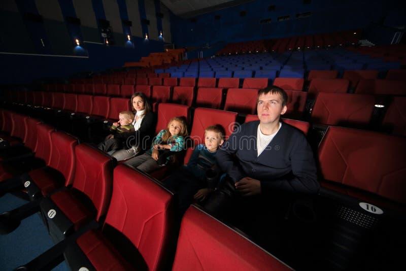 Pai e mãe com as crianças que olham o filme foto de stock