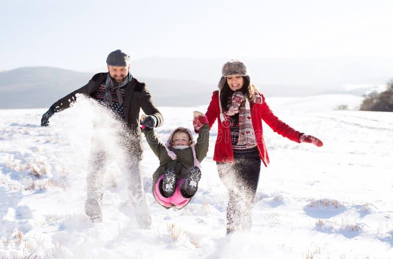 Pai e mãe com sua filha, jogando na neve imagem de stock