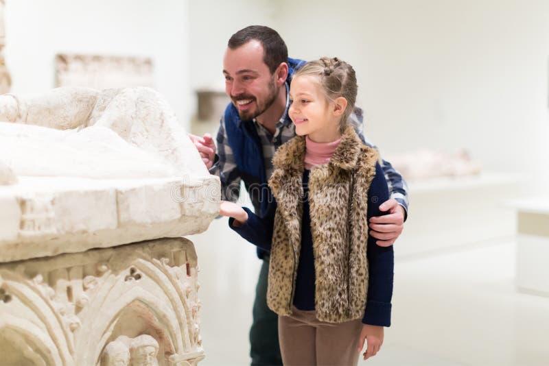 Pai e menina pequena que exploram bas-relevos velhos fotografia de stock