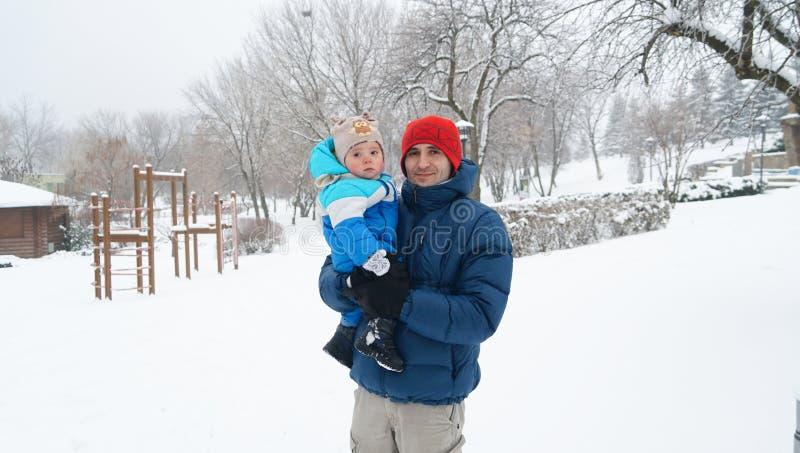 Pai e menino em um dia de inverno frio Conceito de família Posses do paizinho imagens de stock royalty free