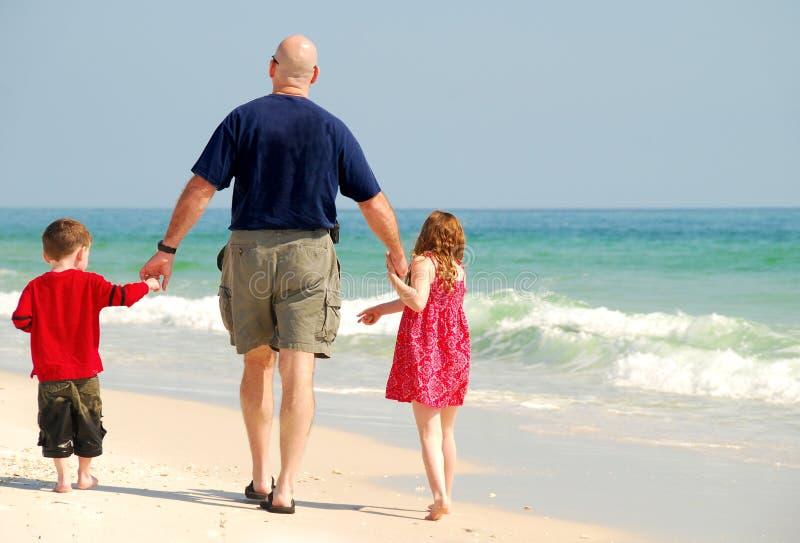 Pai e miúdos na praia imagens de stock
