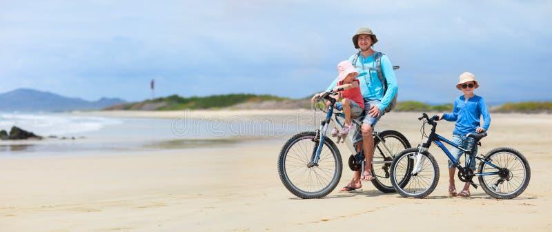 Pai e miúdos que montam bicicletas imagens de stock royalty free