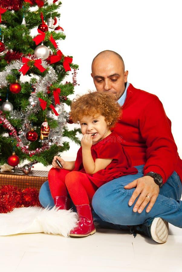 Pai e paizinho que sentam-se perto da árvore do Xmas fotografia de stock royalty free