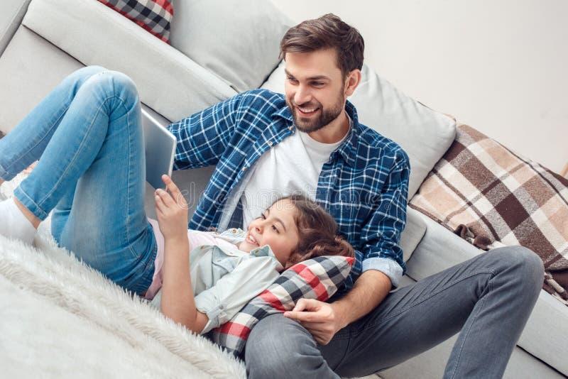 Pai e pouca filha em casa na menina do assoalho que encontra-se nos pés do pai que jogam o jogo na tabuleta digital alegre foto de stock