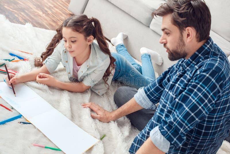 Pai e pouca filha em casa no homem do assoalho que olha a imagem do desenho da menina com lápis imagem de stock
