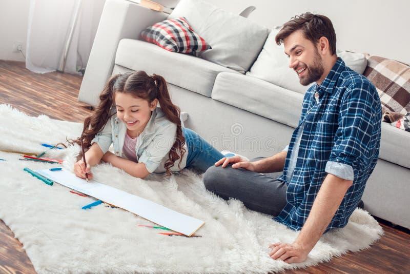 Pai e pouca filha em casa no homem do assoalho que olha o desenho da filha no sorriso do álbum imagens de stock royalty free