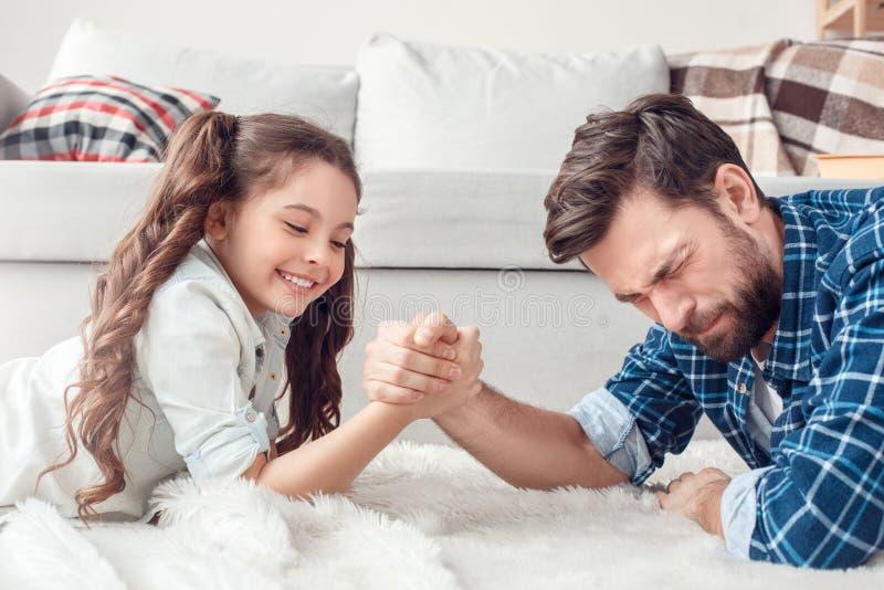 Pai e pouca filha em casa que encontram-se na luta do assoalho brincalhão fotografia de stock royalty free