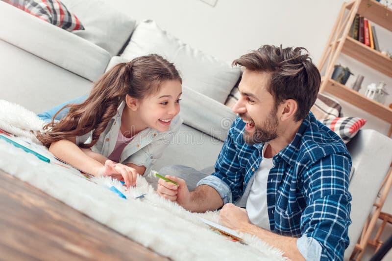 Pai e pouca filha em casa que encontram-se no assoalho que mantém os lápis que olham se alegres imagem de stock