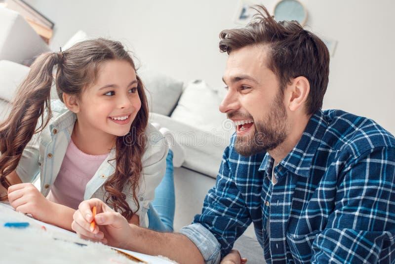 Pai e pouca filha em casa que encontram-se no close-up feliz de sorriso de fala do desenho do assoalho fotos de stock royalty free