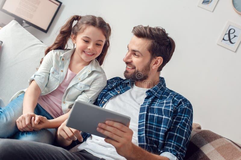 Pai e pouca filha em casa que sentam a aplicação da exibição do homem na tabuleta digital à menina alegre fotografia de stock royalty free