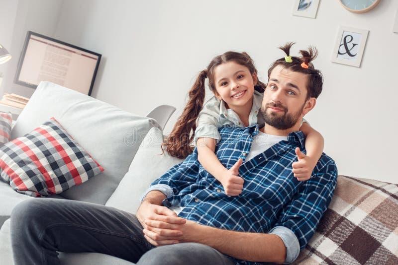 Pai e pouca filha em casa que sentam a menina que abraça o pai com os polegares alegres do penteado engraçado acima foto de stock royalty free