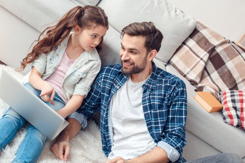 Pai e pouca filha em casa que sentam a menina que aponta no portátil surpreendido fotografia de stock royalty free