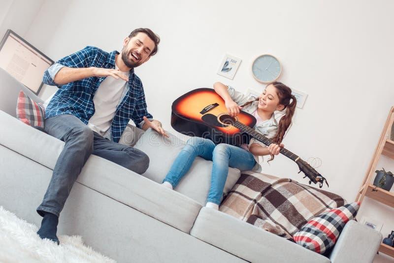 Pai e pouca filha em casa que sentam a menina que canta com o pai alegre fotos de stock