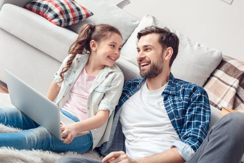 Pai e pouca filha em casa que sentam a menina com o portátil que olha o pai alegre foto de stock royalty free