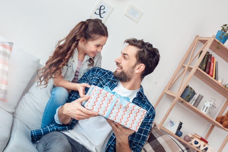 Pai e pouca filha em casa que sentam a menina que dá o presente de aniversário do pai feliz imagem de stock royalty free