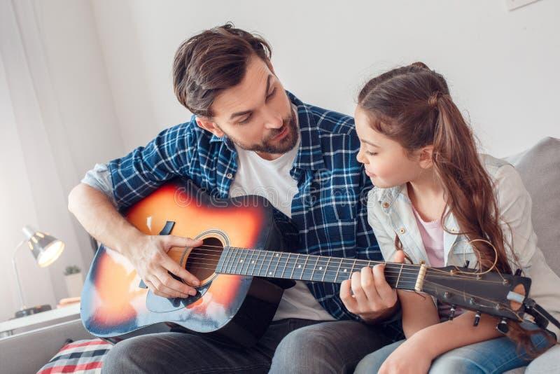 Pai e pouca filha em casa que sentam a menina de explicação do homem como jogar a guitarra imagens de stock