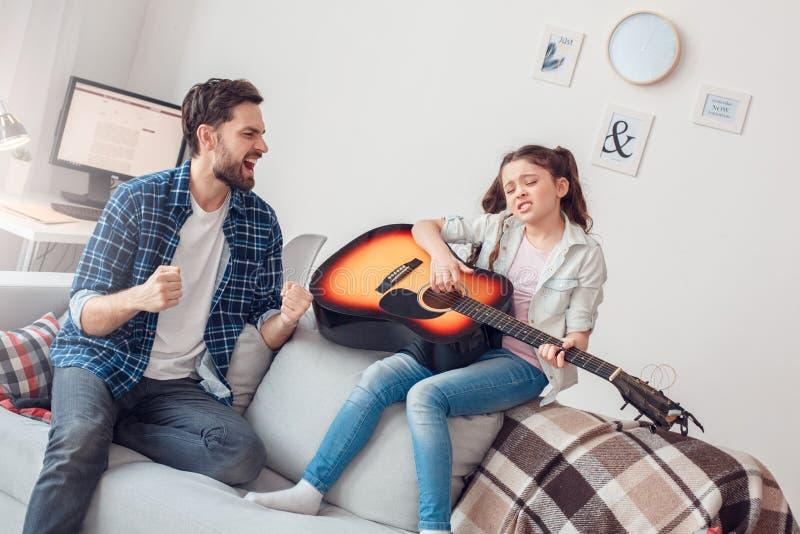 Pai e pouca filha em casa que sentam a menina que joga a guitarra que canta tendo o divertimento imagens de stock royalty free