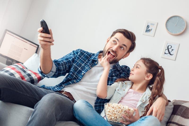 Pai e pouca filha em casa que sentam o canal do interruptor do homem quando filha que dá lhe a pipoca alegre imagem de stock