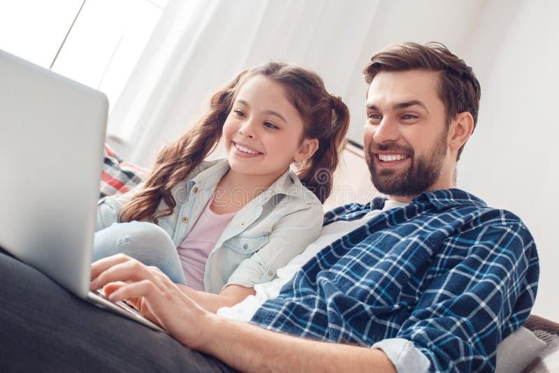 Pai e pouca filha em casa que sentam o funcionamento no close-up do portátil imagens de stock