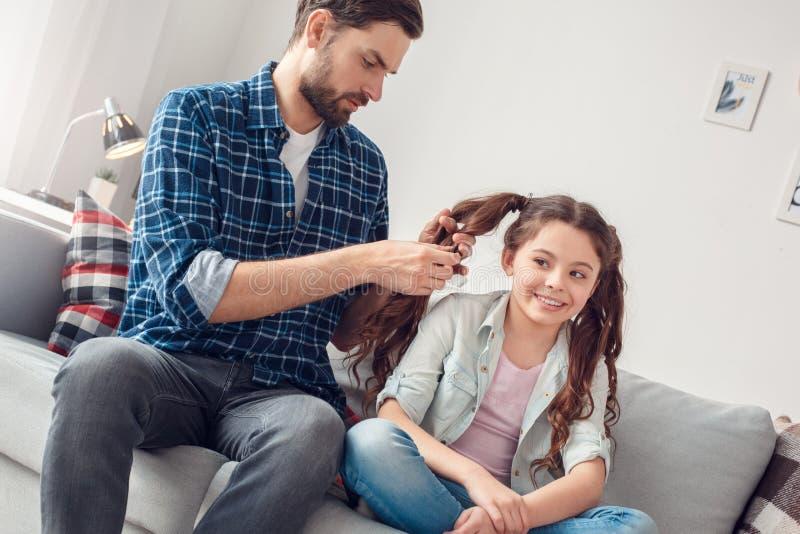 Pai e pouca filha em casa que sentam o homem que faz tranças à filha concentrada fotografia de stock