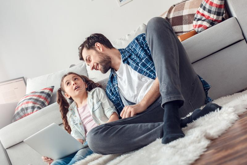 Pai e pouca filha em casa que sentam o homem que olha a filha com o portátil referido imagens de stock