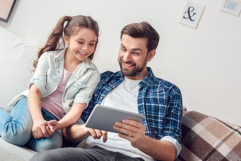 Pai e pouca filha em casa que sentam o vídeo de observação em linha na tabuleta digital imagens de stock