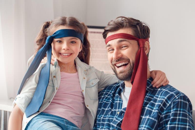 Pai e pouca filha em casa que sentam os laços vestindo que riem o close-up fotografia de stock