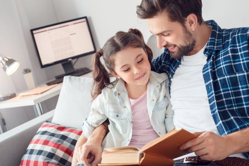 Pai e pouca filha em casa que sentam-se abraçando o conto de fadas da leitura do homem ao close-up feliz da filha fotografia de stock