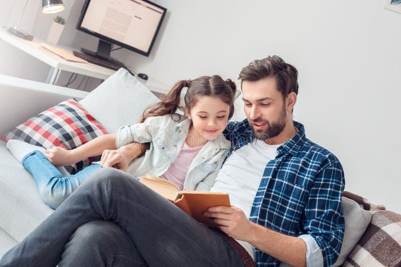 Pai e pouca filha em casa que sentam-se abraçando o livro de leitura do homem alto à filha alegre imagens de stock