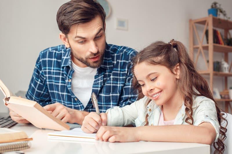 Pai e pouca filha em casa que sentam-se na menina de ajuda do pai da tabela com trabalhos de casa fotografia de stock royalty free