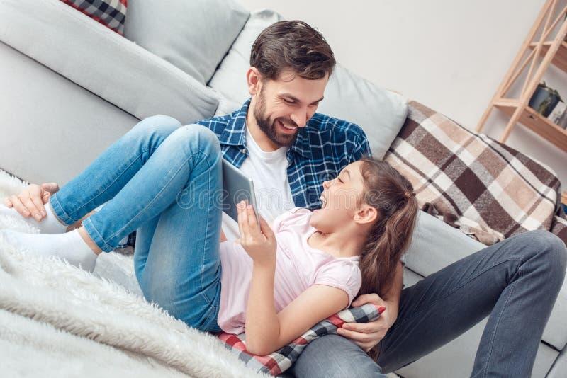 Pai e pouca filha em casa que sentam-se na menina do assoalho que guarda a tabuleta digital que ri olhando o pai imagens de stock
