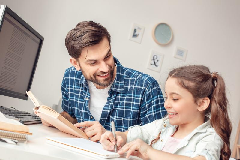 Pai e pouca filha em casa que sentam-se na menina do ensino do homem da tabela feliz foto de stock