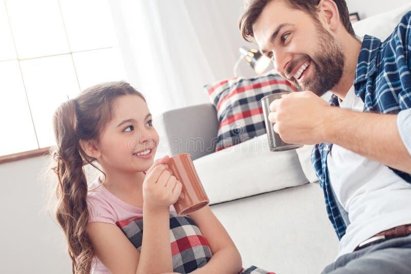 Pai e pouca filha em casa que sentam-se no assoalho que bebe o sorriso quente do chá brincalhão fotos de stock