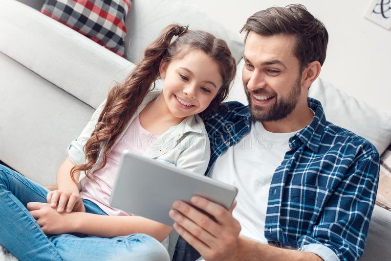 Pai e pouca filha em casa que sentam-se no vídeo de observação do assoalho no close-up alegre da tabuleta digital fotografia de stock