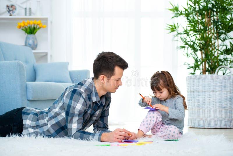 Pai e pouca filha que têm o tempo da família da qualidade junto em casa paizinho com a menina que encontra-se no desenho morno do imagens de stock