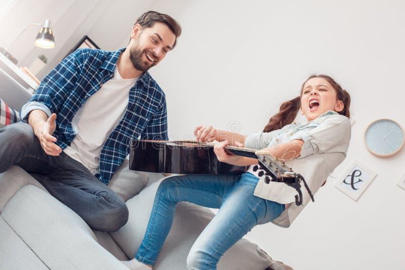 Pai e pouca menina da filha em casa que fazem o concerto para o pai imagem de stock