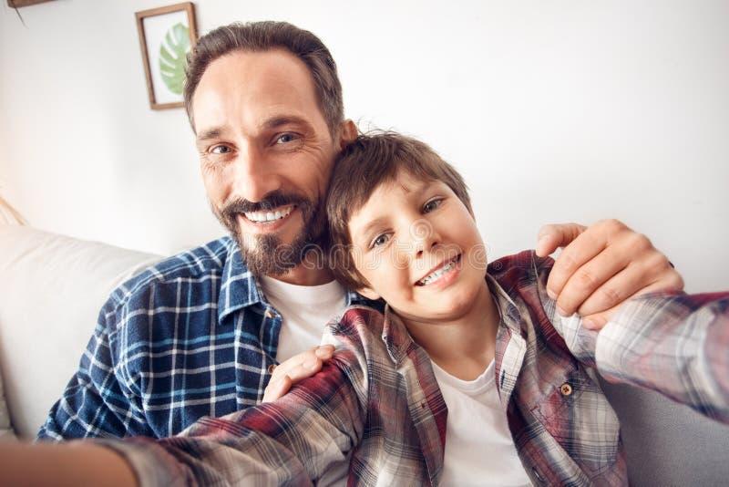 Pai e pouco filho em casa que sentam o aperto tomando o selfie no smartphone que olha o close-up feliz da câmera imagem de stock royalty free