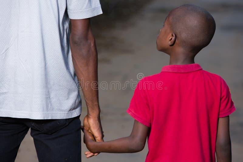 Pai e pouco filho que guardam as mãos que andam em uma estrada foto de stock