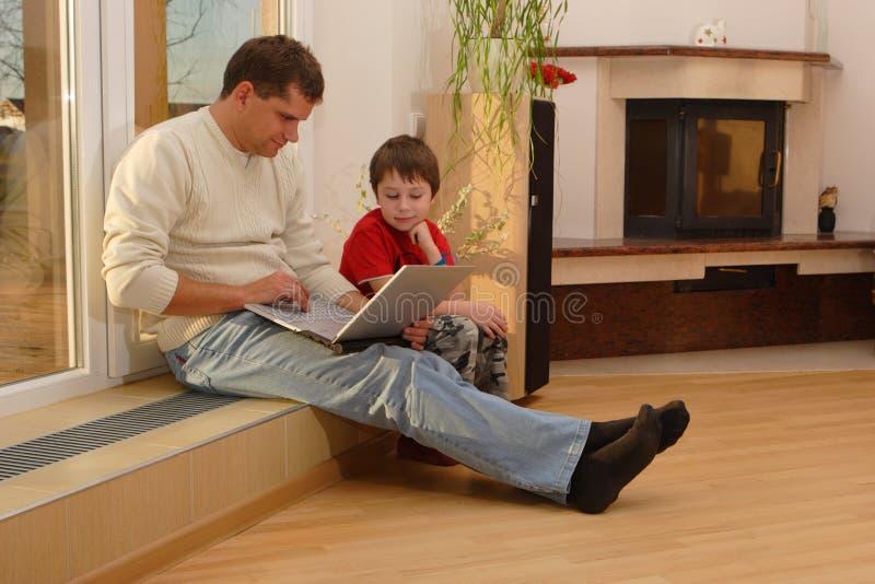 Pai e seu filho com portátil imagem de stock royalty free