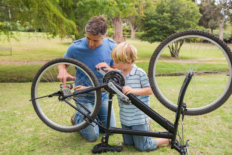 Pai e seu filho que fixam uma bicicleta imagem de stock