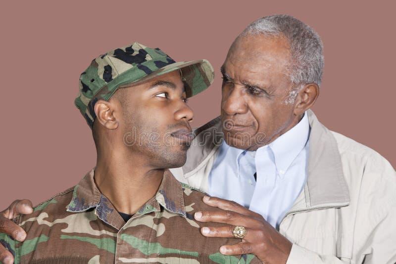 Pai e soldado dos E.U. Marine Corps que olha se sobre o fundo marrom fotografia de stock royalty free
