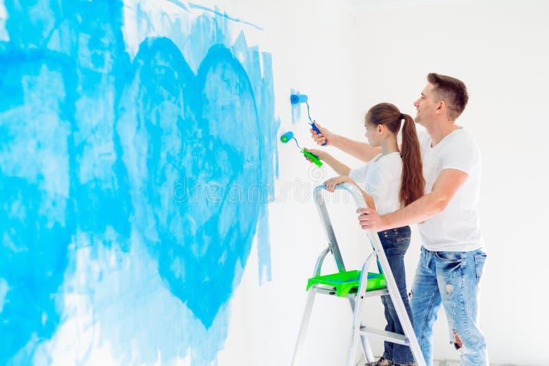 Pai e sua filha pequena que pintam uma parede na casa nova imagem de stock royalty free