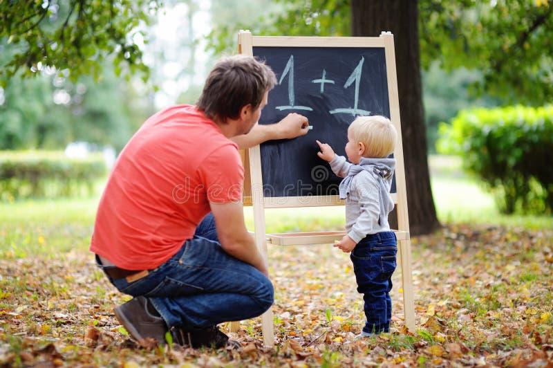 Pai e sua matemática praticando do filho da criança imagens de stock