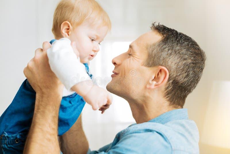 Pai emocional bonito que sorri e que tenta beijar seu bebê adorável imagens de stock royalty free